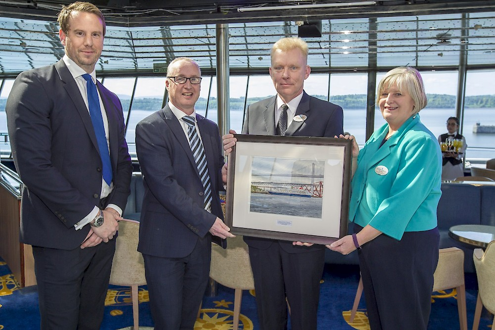 Captain Lars Kjeldsen, Master of Fred. Olsen Cruise Lines' flagship Balmoral (second from right), presents Stuart Wallace, Chief Operating Officer of Forth Ports (second from left), with a special commemorative painting of Balmoral at a VIP Reception on board in the Port of Rosyth on 16th May 2018, along with Fred. Olsen's Clare Ward, Director of Product and Customer Service, and Robert Mason, Capital Cruising's Head of Cruise at Rosyth. [Photo credit: Peter Devlin]